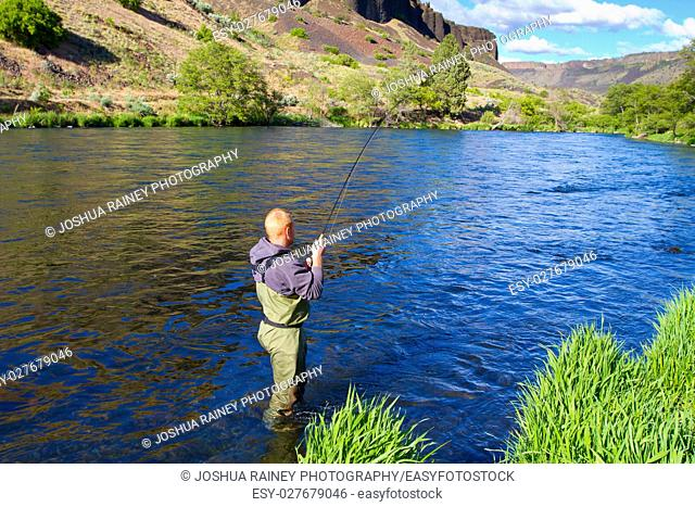 An experienced fly fisherman wades in the water while fly fishing the Deschutes River in Oregon