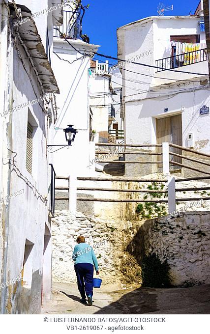 Woman walking through a whitewashed lane of Laroles village in Las Alpujarras. Granada, Andalusia, Spain
