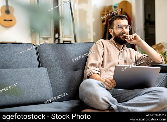 Young man sitting at home on couch, using digital tablet