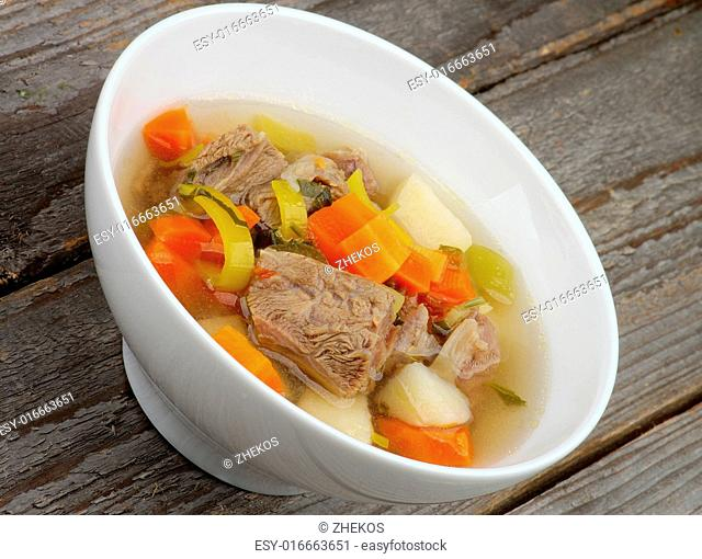 Rustic Beef Soup with Potato, Carrot, Leek and Greens in White Bowl closeup on Wooden background