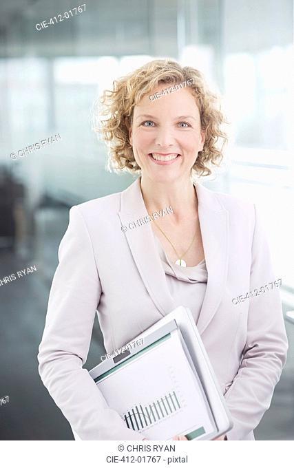 Businesswoman smiling in office hallway