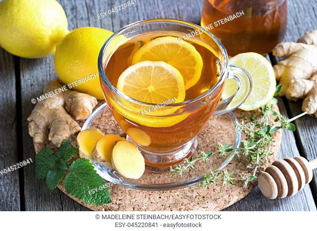 A cup of tea with ginger, lemon, honey and herbs