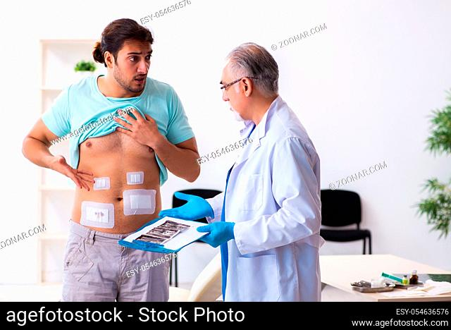 Injured man visiting experienced male doctor