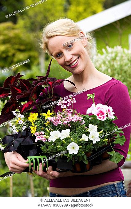 Woman holding a range of different flower pots