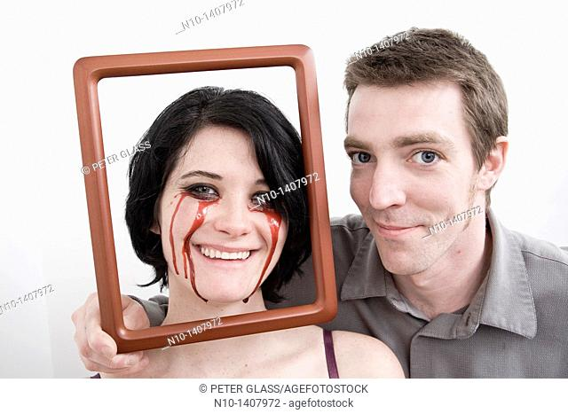 Man holding frame in front of wife, who has blood dripping from her eyes