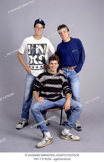 studio portrait full length of three happy teenage boys