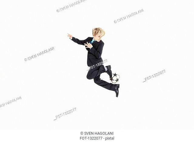 Full length of boy dressed as businessman playing soccer against white background