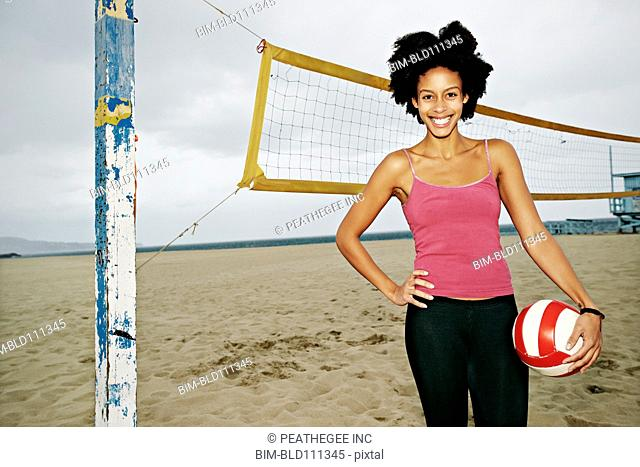 Mixed race woman holding volleyball on beach