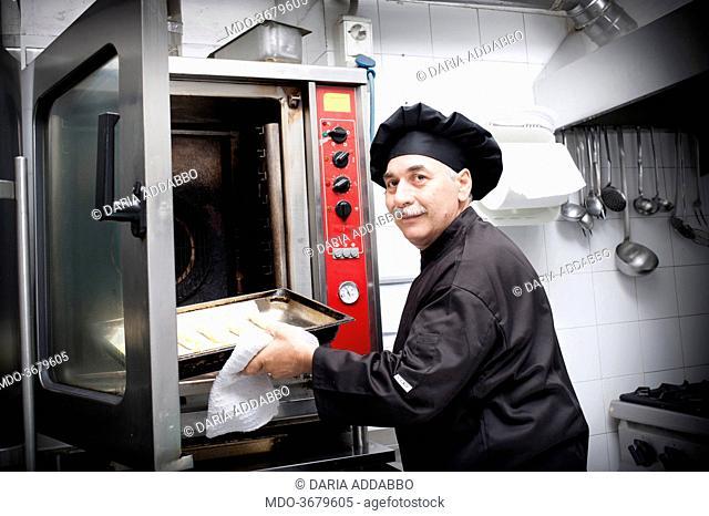 Argentine chef Pascual Juliano of Roman restaurant La Caletta preparing empanadas (the same he prepared for Pope Francis) putting them in the oven