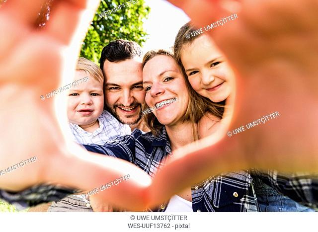 Portrait of happy family looking through finger frame