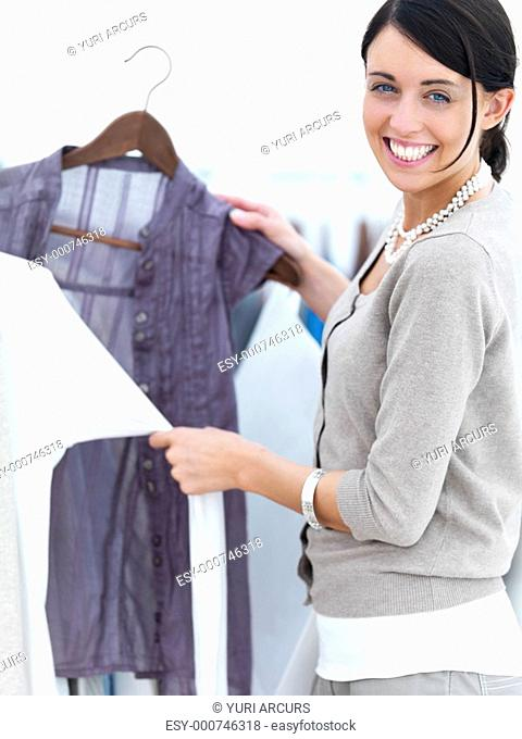 Portrait of a young woman selecting clothes