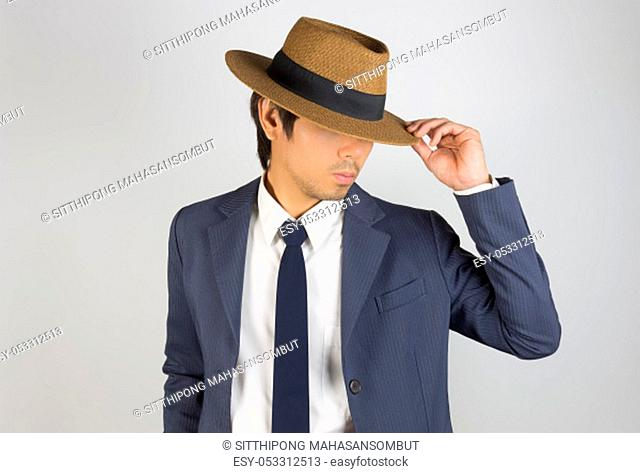 Young Asian Portrait Businessman in Navy Blue Suit Touch Hat Brim and Look Below on Grey Background