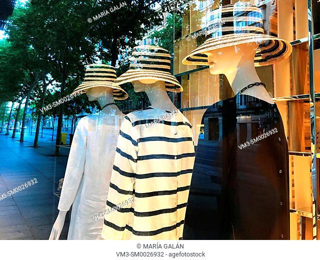 Three mannequins wearing hat in a shop window. Madrid, Spain