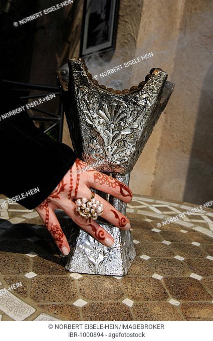 Hand with henna-painting holding incense holder, Dubai, United Arab Emirates, Middle East
