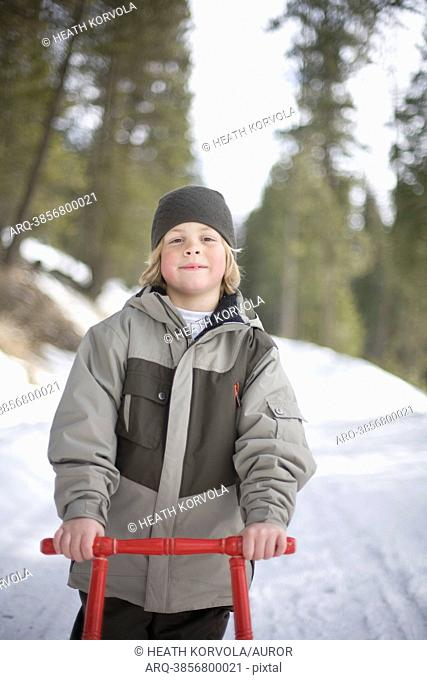 A portrait of a young boy and his sled outside on a snowy road