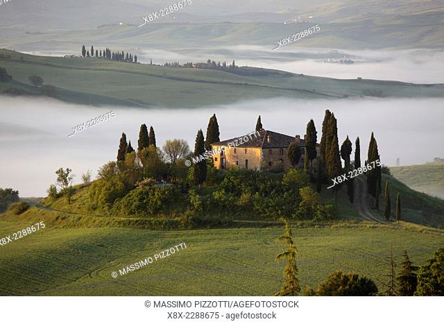 The Belvedere farmhouse in Val d'Orcia with early morning fog, San Quirico d'Orcia, Tuscany, Italy