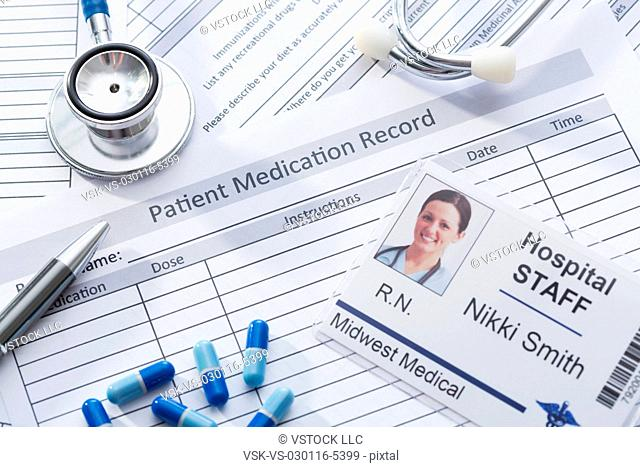 Stethoscope, pills and name tag on medical record