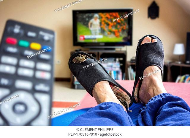 Remote control and couch potato, lazy man in comfy chair wearing worn slippers with big toes sticking through and watching television in living room