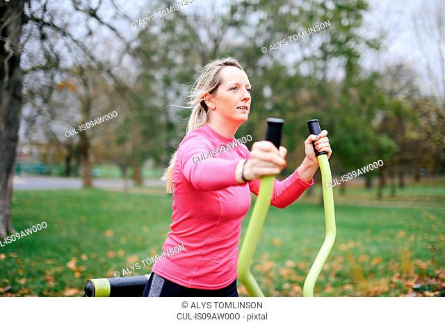 Young woman training on exercise machine in park