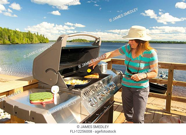 A woman cooks a meal on a barbeque on a deck overlooking a beautiful lake; Ontario, Canada