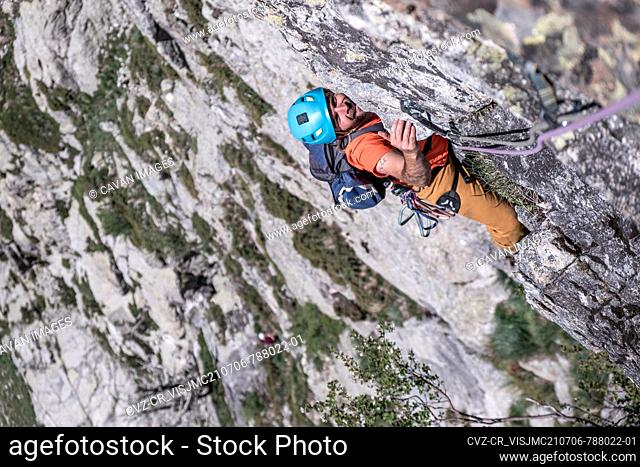 boy climbing multipich on granite rock in the pyrenees