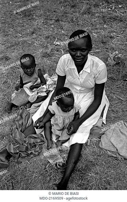 Portrait of a Kenyan woman with two children. Kenya, 1960s