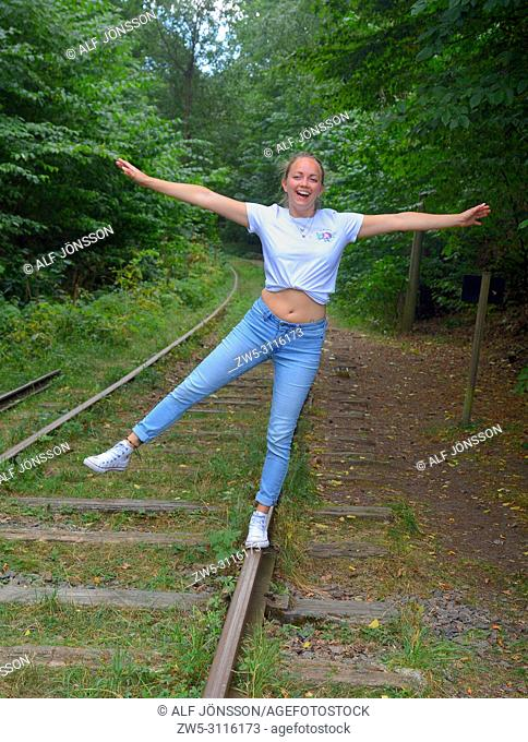Young woman, 25 years old, balancing on a railroad track in Fyledalen, Scania, Sweden; Europe