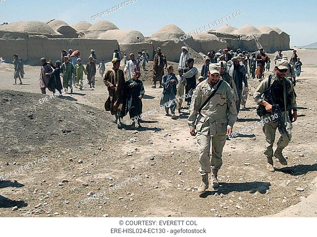 Villagers from Nojoy outside Kandahar International Airport follow the members of the U.S. Army's Tactical Psychological Operations Team as they leave after...