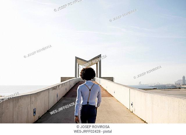 Spain, Barcelona, back view of man walking on a bridge