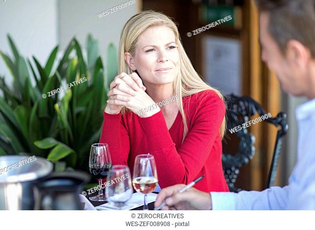 Man and woman sitting at table drinking wine