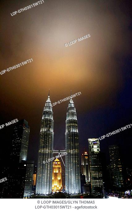 Petronas Towers in Kuala Lumpur with a stormy sky behind at sunset