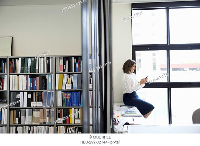 Businesswoman texting with cell phone at office window