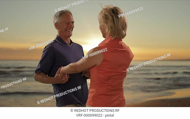 senior couple hugging on beach with sunset and sea background