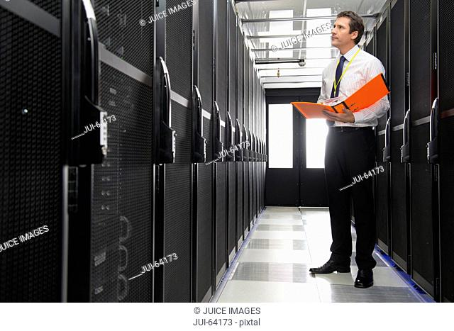 Manager with folder, checking aisle of storage cabinets in data center