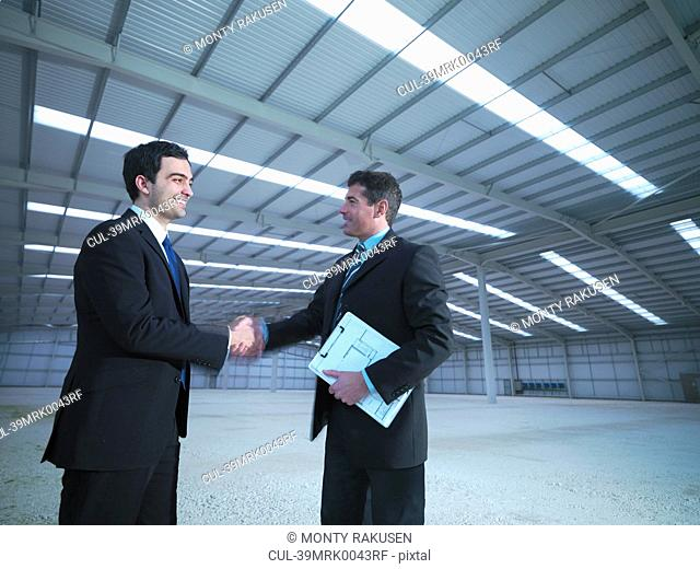 Businessmen shaking hands in warehouse