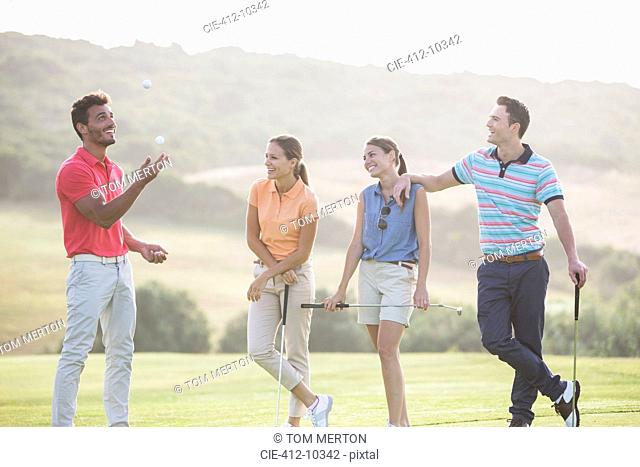 Friends juggling golf balls on golf course