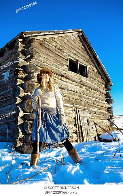 A Girl With A Fur Hat Stands In The Snow With A Walking Stick And A Log Cabin In The Background; Homer, Alaska, United States Of America