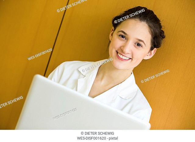 Portrait of smiling teenage girl in doctor's overall with laptop