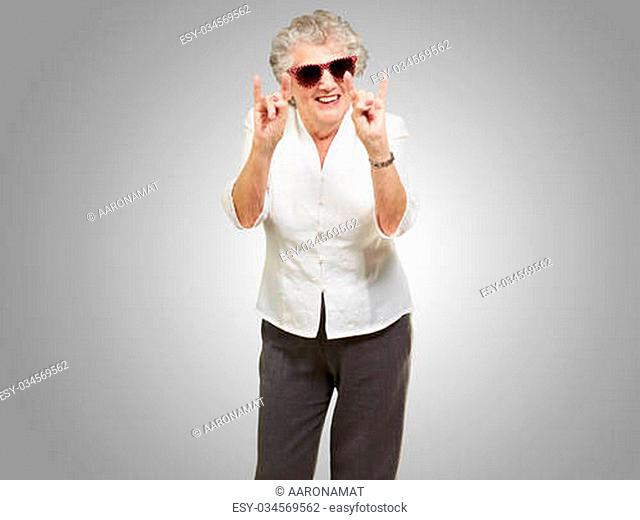 portrait of a happy senior woman doing rock symbol over grey background