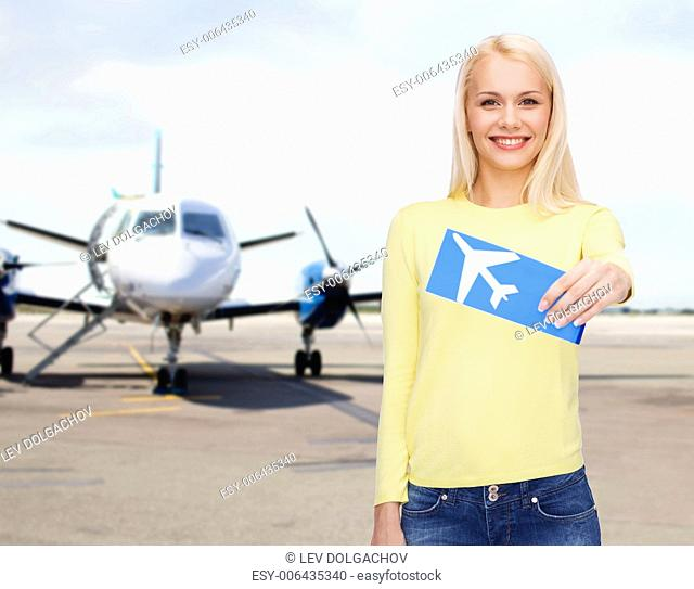 travel, people and transportation concept - smiling young woman with airplane ticket at airport