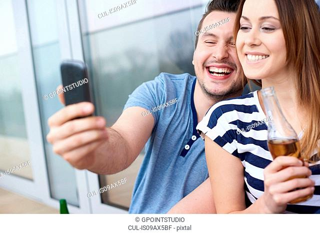 Young couple sitting outdoors, taking self portrait, using smartphone