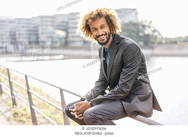Young businessman sitting on railing