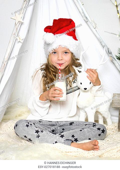 girl drinking milk with santa hat in the studio