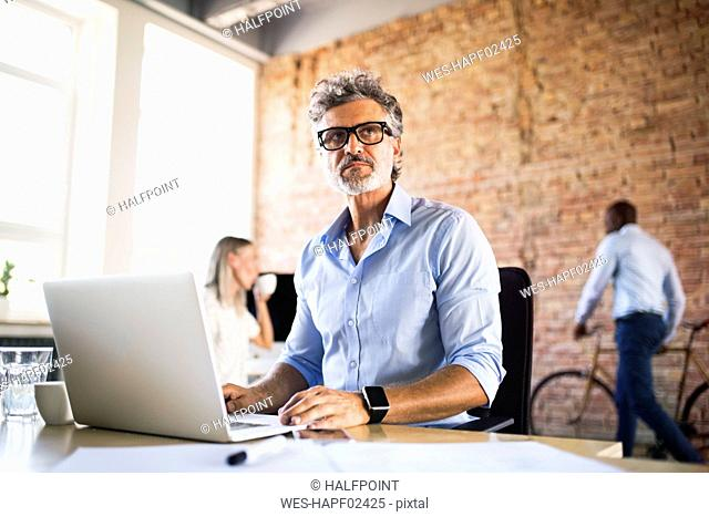 Businessman using laptop in office with colleagues in background