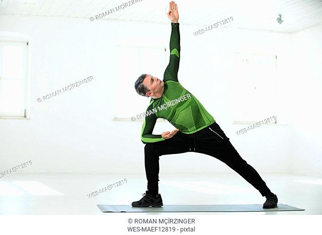 Man doing his fitness regime, practising yoga poses