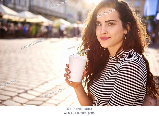 Portrait of beautiful young woman with takeaway coffee in the city