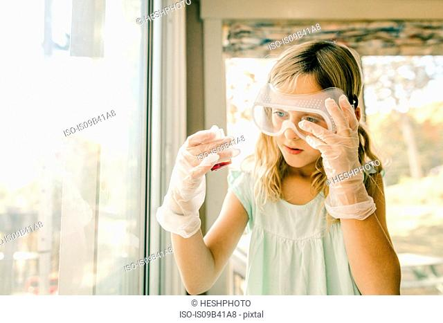 Girl doing science experiment, staring at measuring flask