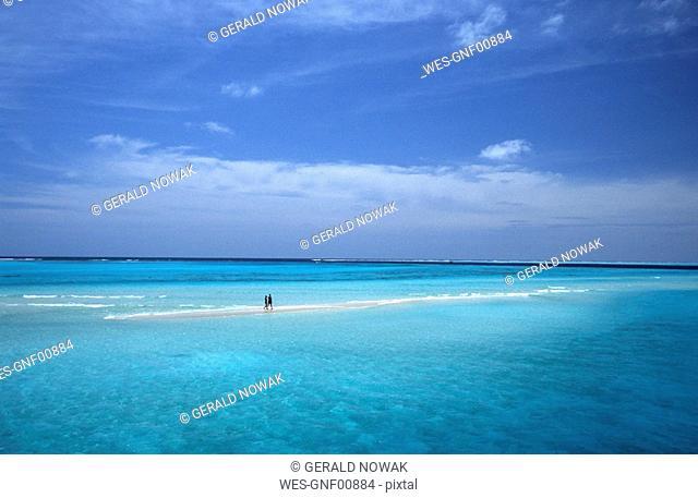 Maldives, couple walking on sand bank