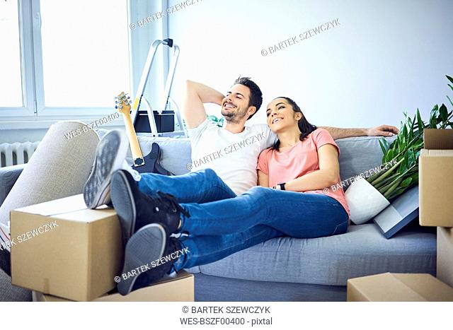 Happy couple sitting on couch surrounded by cardboard boxes