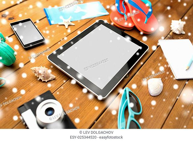 winter holidays, tourism, technology and objects concept - close up of tablet pc computer and travel stuff over snow